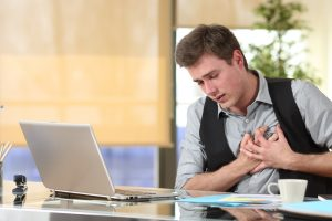 man suffering from heart disease clutching his chest while working