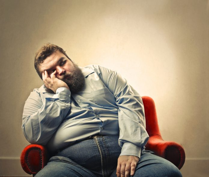 sad obese man sitting on chair learns about Progentra supplements