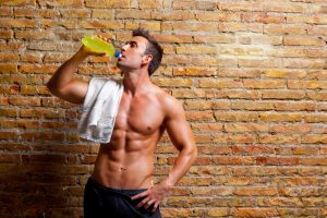 fit shirtless guy drinking sports drink