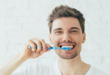 guy happy brushing his teeth