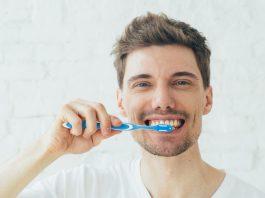 guy happy brushing his teeth