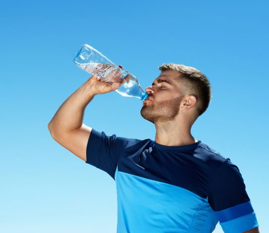a guy drinking a bottle of water