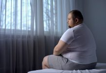 sad obese man sits on bed